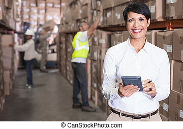 Pretty warehouse manager using calculator in a large...