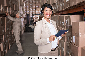 Pretty warehouse manager using tablet pc in a large...
