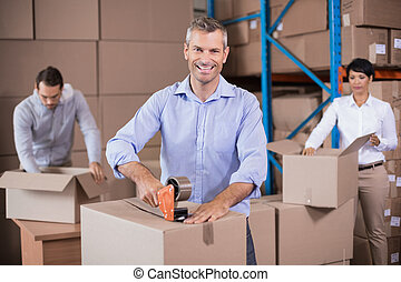 Warehouse workers packing up boxes in a large warehouse