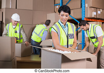 Warehouse workers in yellow vests preparing a shipment in a...