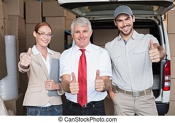 Warehouse managers and delivery driver smiling at camera in...