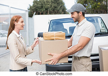 Delivery driver passing parcels to happy customer outside...