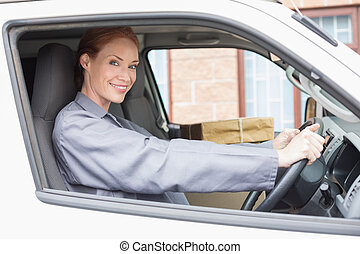Delivery driver smiling at camera in her van outside the...
