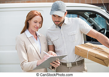 Delivery driver showing where to sign to customer outside...