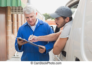 Delivery driver showing customer where to sign outside the...