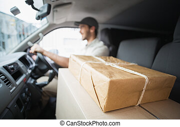 Delivery driver driving van with parcels on seat outside the...