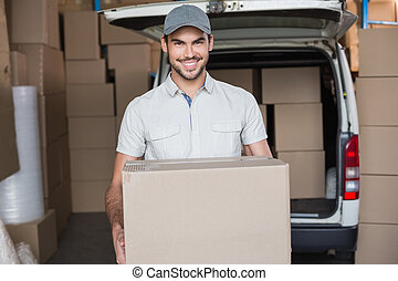 Delivery driver smiling at camera holding box in a large...