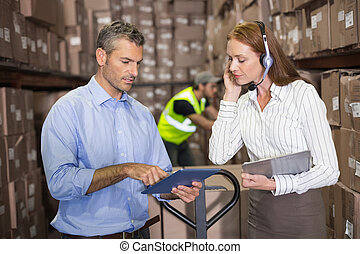 Warehouse manager and foreman working together in a large...