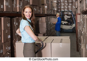 Warehouse manager smiling at camera with trolley in a large...
