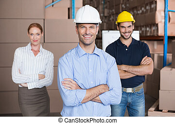 Warehouse team smiling at camera in a large warehouse