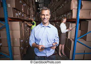 Warehouse manager smiling at camera in a large warehouse