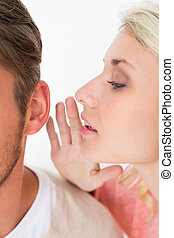 Woman whispering secret into a mans ear - Close up of a...