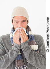 Young man in warm clothing sneezing - Portrait of young man...