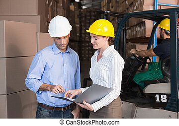 Warehouse manager talking with colleague in a large...