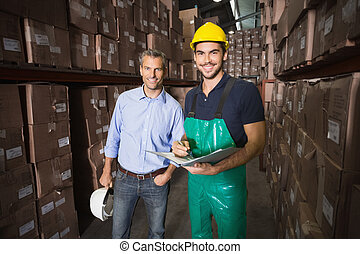 Warehouse manager smiling at camera with worker in a large...