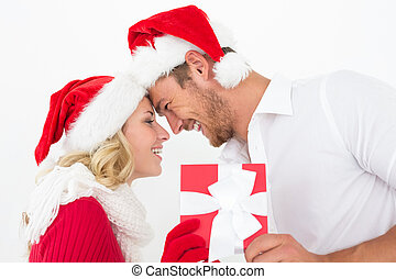 Attractive couple wearing santa hats with gift - Side view...