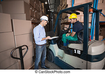 Warehouse manager talking with forklift driver in a large...