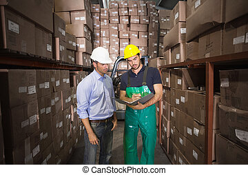 Warehouse manager talking with worker