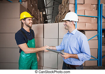 Warehouse worker loading up a pallet with manager in a large...