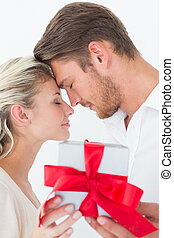 Attractive young couple holding gift over white background