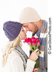 Attractive couple in warm clothing holding flowers -...