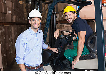 Warehouse manager smiling at camera with forklift driver in...