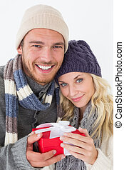 Attractive couple in warm clothing holding gift - Attractive...