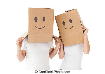 Couple wearing happy face boxes over heads against white...
