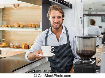 Handsome barista offering a cup of coffee to camera at the...