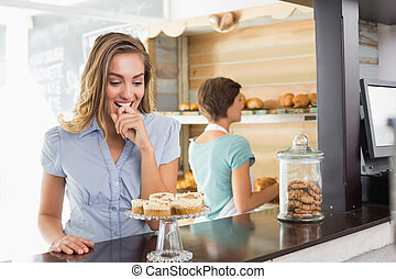 Pretty blonde being tempted by cupcakes at the coffee shop
