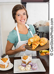 Pretty waitress showing tray of croissants at the coffee...