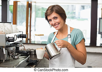 Pretty barista pouring milk into cup of coffee at the coffee...