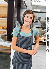 Pretty waitress smiling at camera at the coffee shop