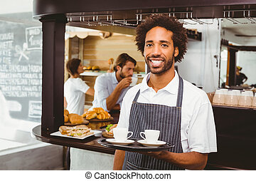 Handsome waiter smiling at camera holding tray at the coffee...