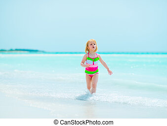 Baby girl running on sea shore