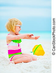 Baby girl in sunglasses applying sun block creme on beach