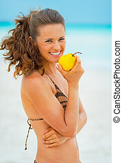 Portrait of happy young woman eating pear on beach