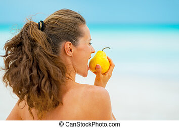 Profile portrait of young woman eating pear on beach