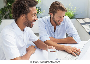 Two friends enjoying coffee together with laptop outside at...