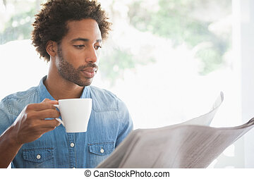 Casual man having coffee while reading newspaper at the...