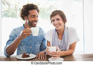 Casual couple having coffee and cake together at the coffee...