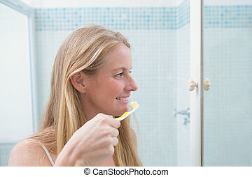 Happy woman brushing her teeth at home in the bathroom
