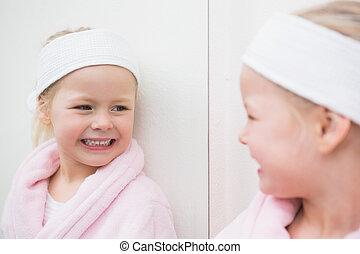 Cute little girl looking in mirror at home in the bathroom