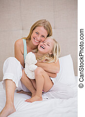 Cute little girl and mother on bed at home in the bedroom