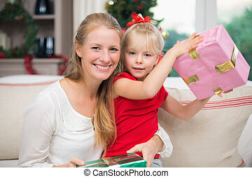 Cute daughter and mother celebrating christmas at home in...