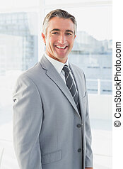 Businessman smiling at the camera from his workplace