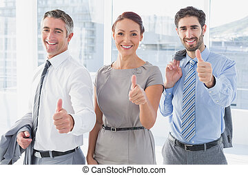 Businesswoman smiling while at work with co-workers and...