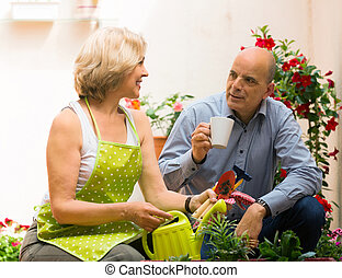 Happy elderly couple drinking coffee at terrace and talking