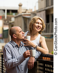 Aged couple drink tea on balcony - Positive smiling aged...