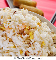 chinese fried rice and springrolls - closeup of a bowl with...